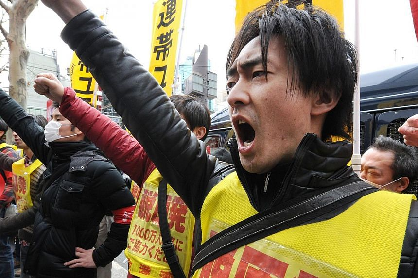 Fukushima nuclear workers and their supporters shouts slogans as they raise their fists in front of the headquarters of Tokyo Electric Power Company (TEPCO), operator of the tsunami-battered Fukushima Daiichi nuclear power plant, during a rally in To