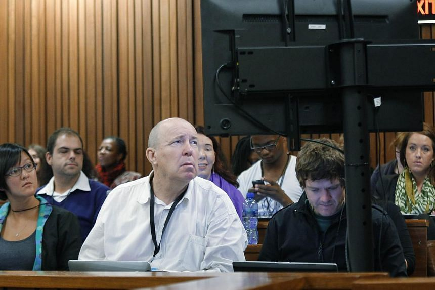 Members of the media look at photographs of the crime scene taken in the house of South African Paralympic athlete Oscar Pistorius during his ongoing murder trial, on March 14, 2014 in Pretoria. Pistorius's murder trial heard that police officers wer