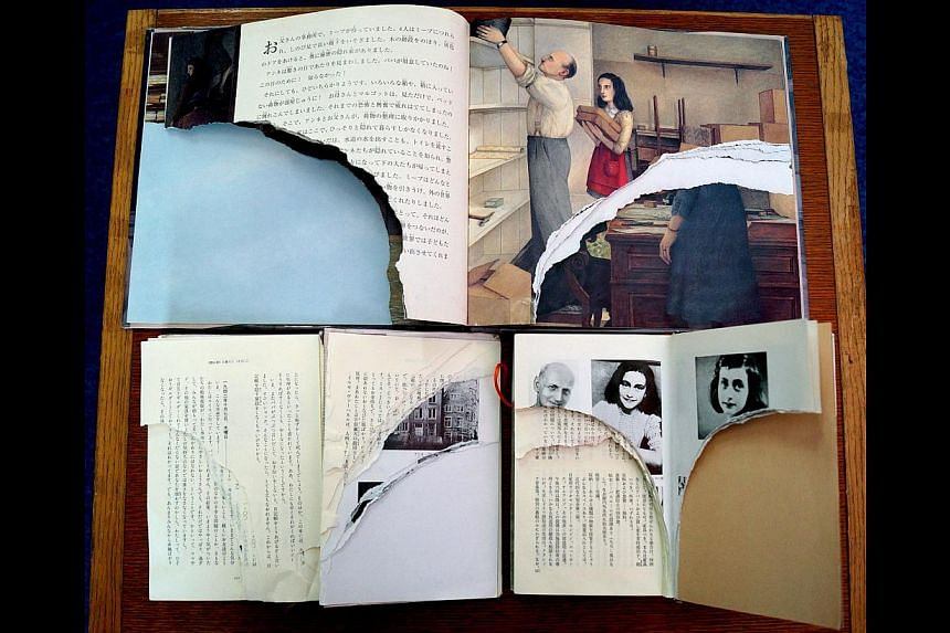 """Ripped pages of three books of Anne Frank's """"Diary of Young Girl"""" are displayed at a library in Tokyo on Feb 21, 2014.A man was arrested Friday for vandalising copies of Anne Frank's """"The Diary of a Young Girl"""" in Tokyo libraries, police said,"""