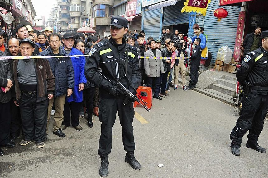 Police stand guard in front of local residents near a crime site on a street in Changsha, Hunan Province, March 14, 2014. Attackers armed with knives killed three people in China Friday, an official said, ruling out terrorism two weeks after a m