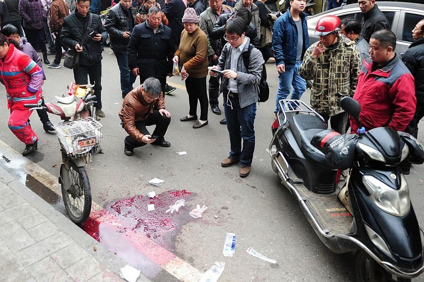 Residents gather at the scene where attackers armed with knives killed three people in Changsha, central China's Hunan province on March 14, 2014.At least six people died after a knifing incident in central China's Changsha city, the state medi