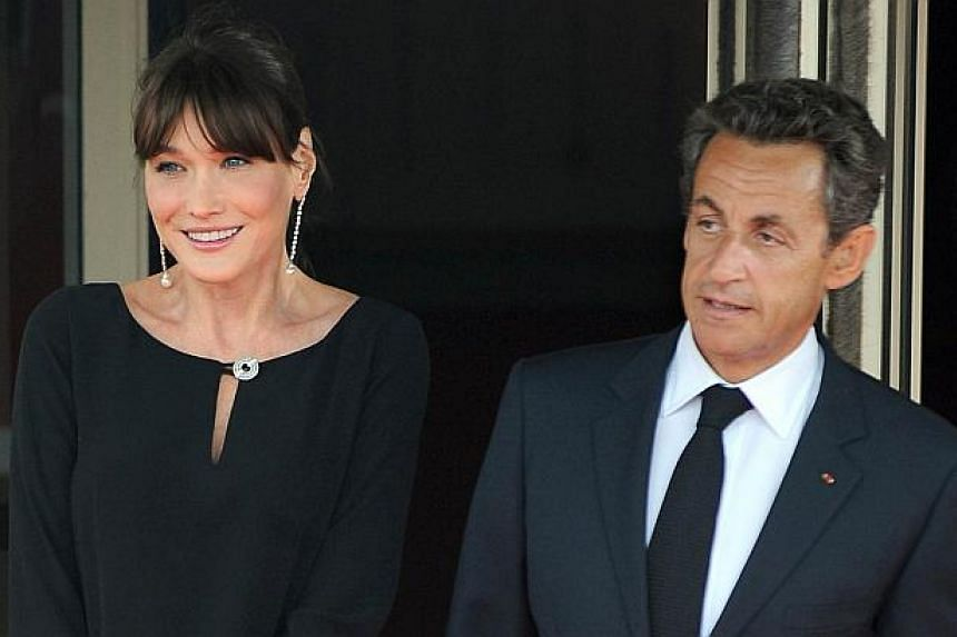 A file picture taken on May 26, 2011, shows French President Nicolas Sarkozy (right) and First Lady Carla Bruni-Sarkozy standing during the G-8 summit in Deauville, France.A French court on Friday ordered a news website to remove the recordings