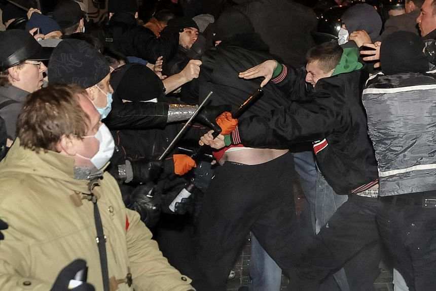 Participants of an anti-war rally (left) clash with pro-Russian supporters during their rallies in Donetsk on March 13, 2014.Russia said on Friday it reserved the right to protect its compatriots in the whole of Ukraine, after a protester was k