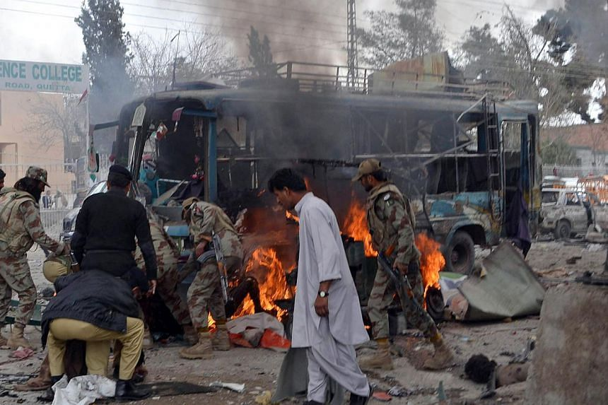 Pakistani paramilitary soldiers and policemen move the blast victims at the site of a bomb explosion in Quetta on March 14, 2014.A bomb blast on Friday killed 10 people and wounded 31 others in Pakistan's restive south-western city of Quetta, o