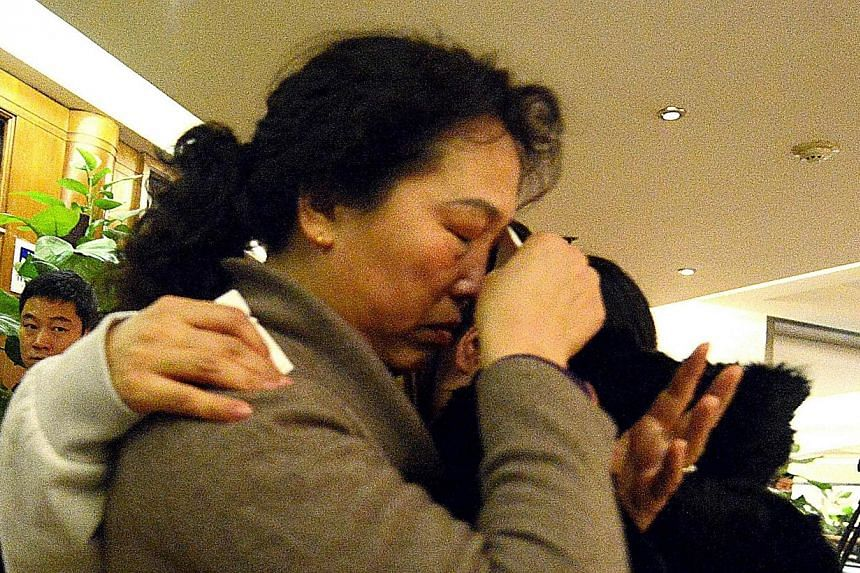 A woman breaks down as she and other relatives of passengers from the missing Malaysia Airlines flight MH370 leave the lounge after getting no new information in Beijing on March 14, 2014. -- PHOTO: AFP