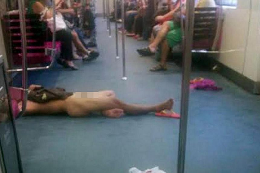 A man who stripped naked on an MRT train on Thursday, March 13, 2014, has been arrested by the police.-- PHOTO: ANG GUAN WEI