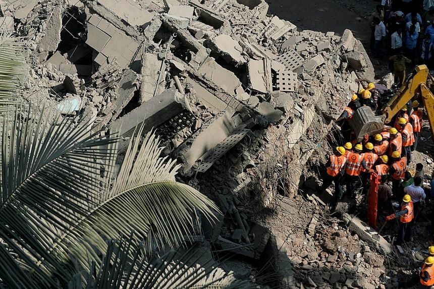Indian National Disaster Relief Force (NDRF) members and firemen look for survivors from the rubble of a collapsed building in Mumbai on Friday, March 14, 2014.An apartment block collapsed in the Indian financial hub of Mumbai on Friday, killin