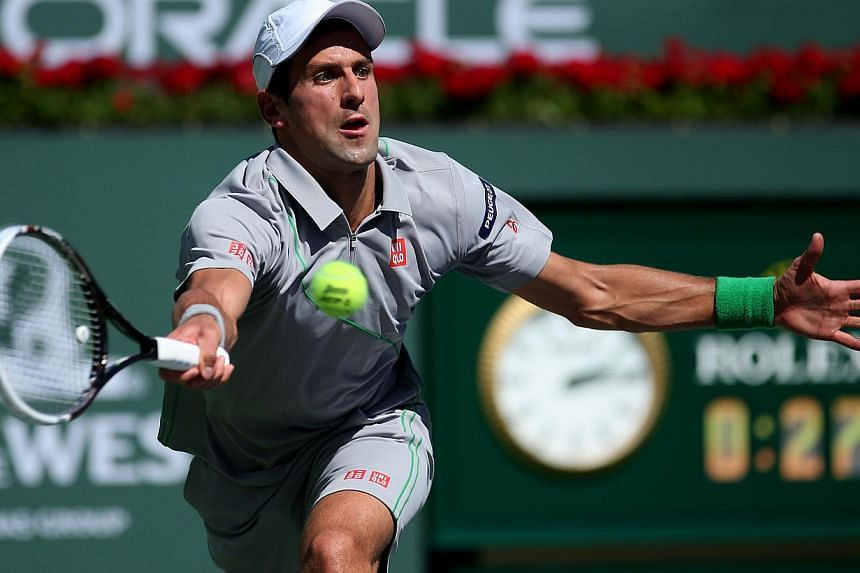Novak Djokovic of Serbia chits a return to Benneteau of France during the BNP Paribas Open at Indian Wells Tennis Garden on March 14, 2014 in Indian Wells, California. -- PHOTO: AFP