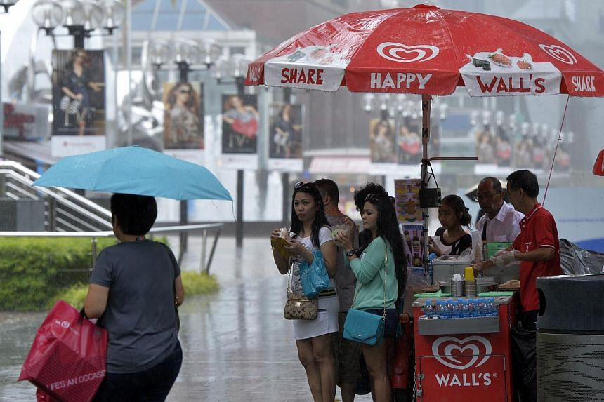 Photos of shoppers scrambling for cover when some light drizzle followed by a sudden 10 minutes of heavy downpour caught many by surprise along Orchard Road.-- ST PHOTO:DESMOND FOO