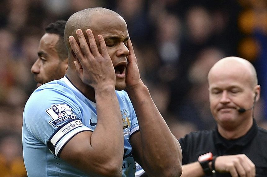 Manchester City's Vincent Kompany (left) reacts after being sent off against Hull City at the KC stadium on March 15, 2014. City survived the 10th-minute dismissal of Kompany to win 2-0 and reduce Chelsea's lead in the Premier League to six points.&n