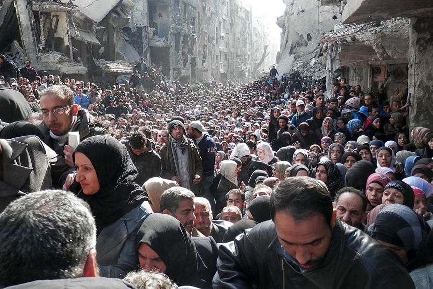 Residents of Syria's besieged Yarmuk Palestinian refugee camp, south of Damascus, crowding a destroyed street during a food distribution led the UN agency, on Jan 31, 2014. Some 30 celebrities have petitioned the UN demanding they take action to prot