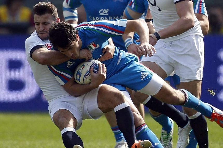 Italy's Leonardo Sarto (centre) is tackled by England's Danny Care during their Six Nations rugby union match at Olympic Stadium in Rome, on March 15, 2014. England scored seven tries in an emphatic 52-11 victory over Italy on Saturday but their hope