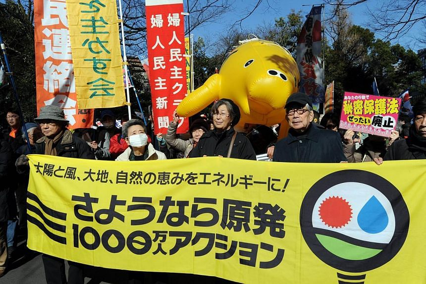 "Japanese author Kenzaburo Oe (third from right) and other leaders carry a banner saying ""Goodbye nuclear power plant"" awaiting for start of the protest march in Tokyo, on March 15, 2014. Thousands of campaigners rallied against nuclear power in Tokyo"