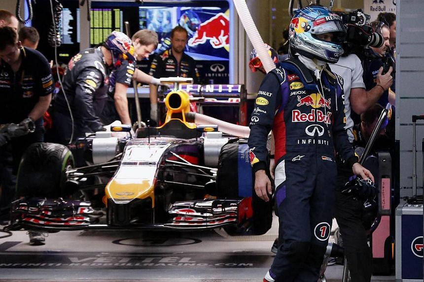 Red Bull driver Sebastian Vettel of Germany walks out of his team garage after the qualifying session of the Formula One Australian Grand Prix in Melbourne, on March 15, 2014. Red Bull were left puzzling over an engine software problem which left For