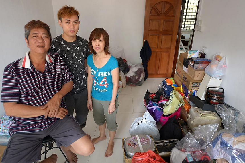 (Right) Mr Tan Kong Lam, 55, his son Tan Wee Kuan, 23, and his wife Foo Siu Chin, 56, in one of the bedrooms of their refurbished flat at Block 33 Jalan Bahagia. The flat was badly damaged (above) by a fire three weeks ago.