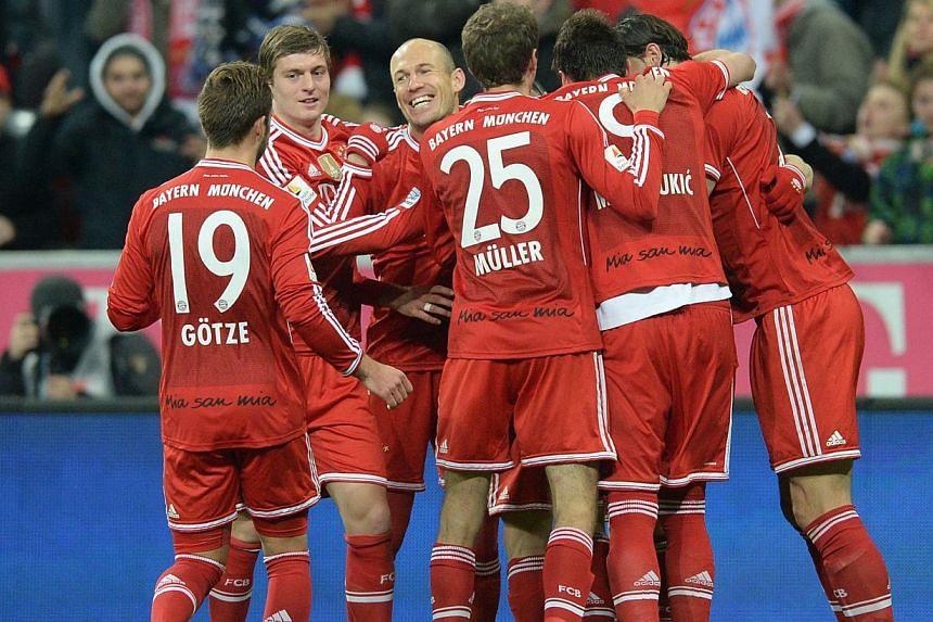 Bayern Munich players celebrate after midfielder Bastian Schweinsteiger scored the 2-0 goal during the German first division Bundesliga football match FC Bayern Munich vs Bayer 04 Leverkusen in Munich, southern Germany, on March 15, 2014. -- PHOTO: A