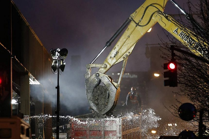 An excavator clears debris at the site of a building explosion in the Harlem section of New York, March 13, 2014. Emergency crews clearing debris from the site of two New York City apartment buildings leveled in a gas explosion said they expected to