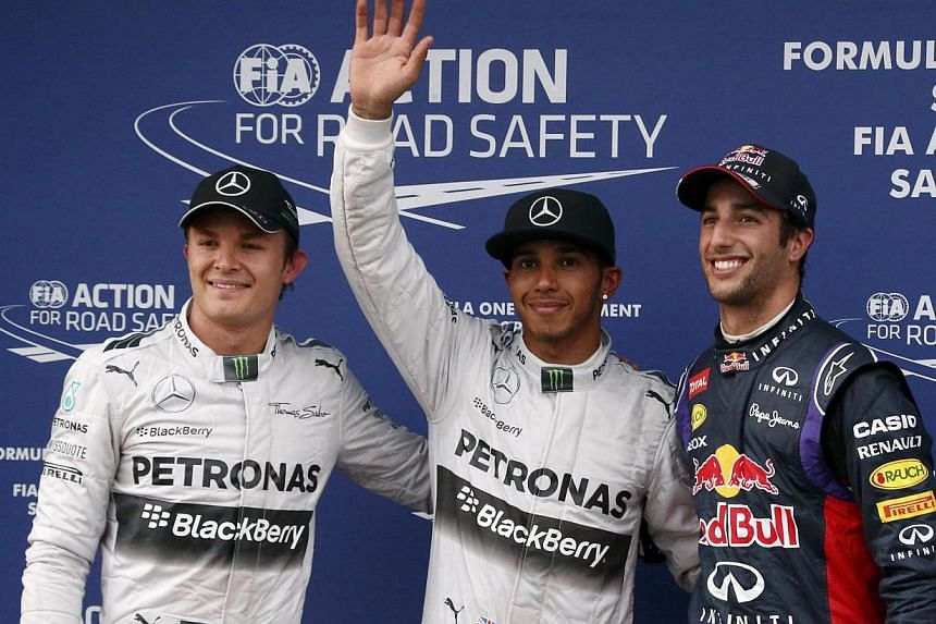 Mercedes Formula One driver Lewis Hamilton of Britain (centre) celebrates taking pole position as he stands beside Red Bull Formula One driver Daniel Ricciardo of Australia and Mercedes Formula One driver Nico Rosberg of Germany, who qualified second