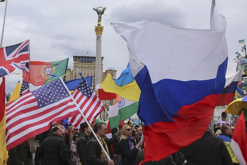 Participants carry flags of different countries during an anti-war rally at Independence Square in Kiev on March 16, 2014. Ukraine's Prime Minister Arseniy Yatsenyuk called on Sunday, March 16, 2014, for foreign observers from the Organisat