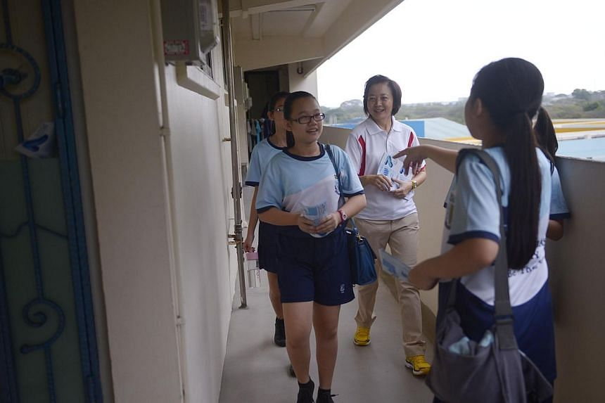 Nee Soon GRC MP Dr Lee Bee Wah (centre) and Naval Base Secondary School students go door-to-door at Block 803 Yishun Ring Road giving out flyers teaching residents how to save water during the dry season, on March 16, 2014. -- ST PHOTO:MARK CHE