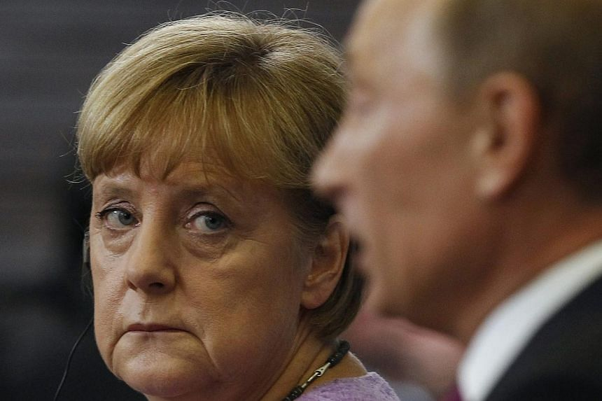 Russian President Vladimir Putin (right) told German Chancellor Angela Merkel on Sunday, March 16, 2014, that the referendum in Ukraine's Crimea complied with international law, the Kremlin said in a statement. -- PHOTO: REUTERS