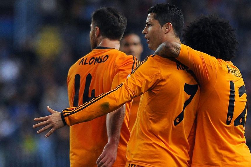 Real Madrid's Portuguese forward Cristiano Ronaldo (centre) celebrates with his teammates Brazilian defender Marcelo (right) and midfielder Xabi Alonso after scoring during the Spanish league football match Malaga CF vs Real Madrid CF at Rosaleda sta