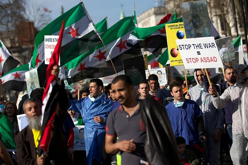 Protesters hold placards and wave the pre-Baath Syrian flag, now used by the Syrian opposition, during a rally outside Downing Street in London on March 15, 2014, to mark the third anniversary since the start of the Syrian conflict. -- PHOTO: AFP&nbs