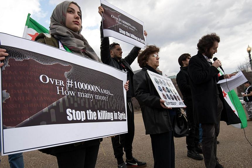 Syrians opposed to President Bashar al-Assad hold signs as a man reads the names of victims as they gather in front of the White House in Washington on March 15, 2014, during a protest to mark the third anniversary of the start of the conflict in Syr