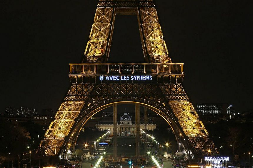 """The words """"With the Syrians"""" are displayed on the Eiffel Tower in Paris on March 15, 2014, in support of Syrians on the third anniversary of the conflict which has claimed more than 140,000 lives. -- PHOTO: REUTERS"""