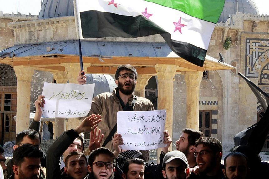 Activists carry flags and signs during a demonstration inside the Umayyad mosque, marking three years since the start of the Syrian uprising, in Aleppo on March 15, 2014. -- PHOTO: REUTERS