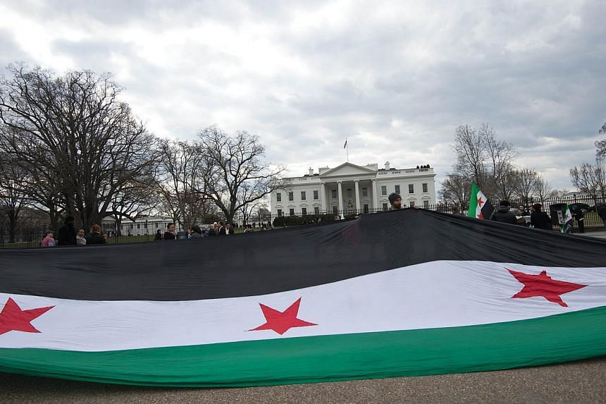 Syrians opposed to President Bashar al-Assad hold a large pre-Baath Syrian flag as they gather in front of the White House in Washington on March 15, 2014, during a protest to mark the third anniversary of the start of the conflict in Syria. -- PHOTO
