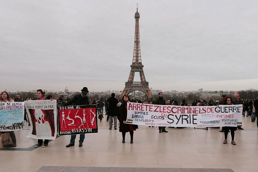 People hold banners as they gather in front of the Eiffel Tower in Paris on March 15, 2014, during a demonstration to mark the third anniversary of the Syria's civil war. -- PHOTO: AFP