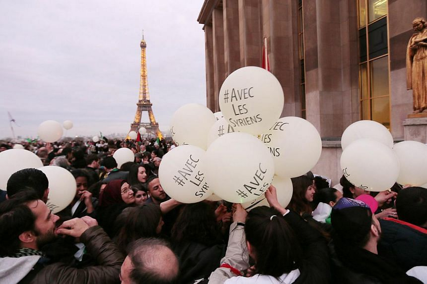 """People hold balloons, with the words """"With the Syrians"""", as they gather in front of the Eiffel Tower during a demonstration to mark the third anniversary of the Syria's civil war on March 15, 2014. -- PHOTO: AFP"""