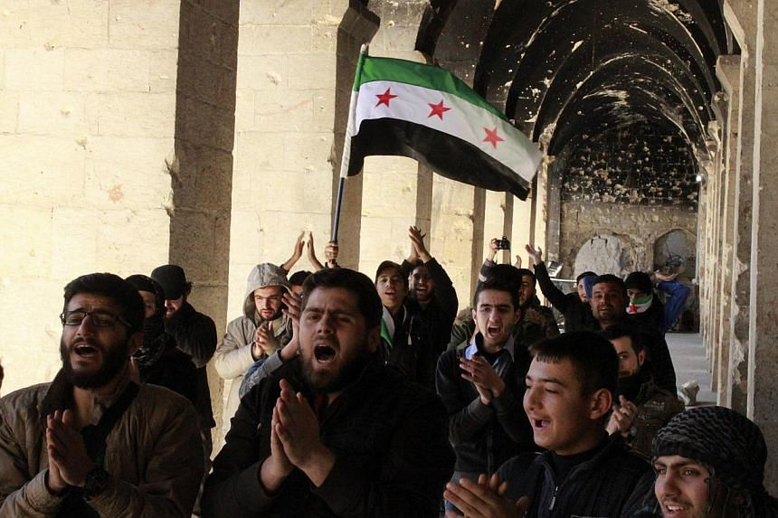Activists carry a flag during a demonstration inside the Umayyad mosque, marking three years since the start of the Syrian uprising, in Aleppo on March 15, 2014. -- PHOTO: REUTERS