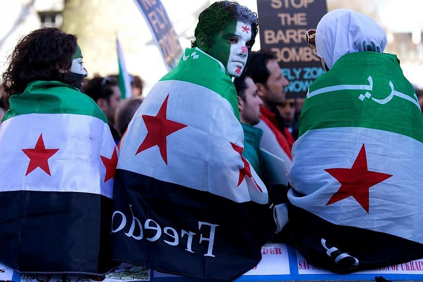 Protesters hold as capes the pre-Baath Syrian flag, now used by the opposition, during a rally outside Downing Street in London on March 15, 2014, to mark the third anniversary since the start of the Syrian conflict. -- PHOTO: AFP
