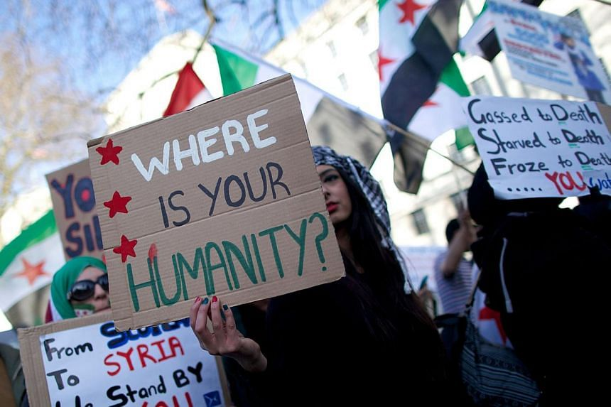 Protesters hold placards and wave the pre-Baath Syrian flag, now used by the Syrian opposition, during a rally outside Downing Street in London on March 15, 2014, to mark the third anniversary since the start of the Syrian conflict. -- PHOTO: AFP