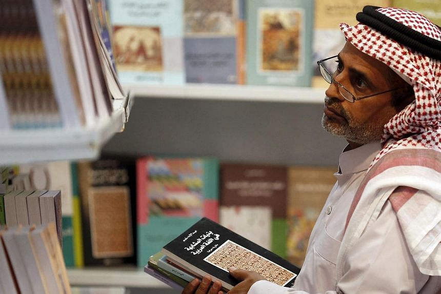 A man looks at books displayed on shelves during a book fair in Riyadh.Saudi authorities have banned hundreds of books, including works by renowned Palestinian poet Mahmud Darwish, as part of a crackdown on publications deemed threatening to th