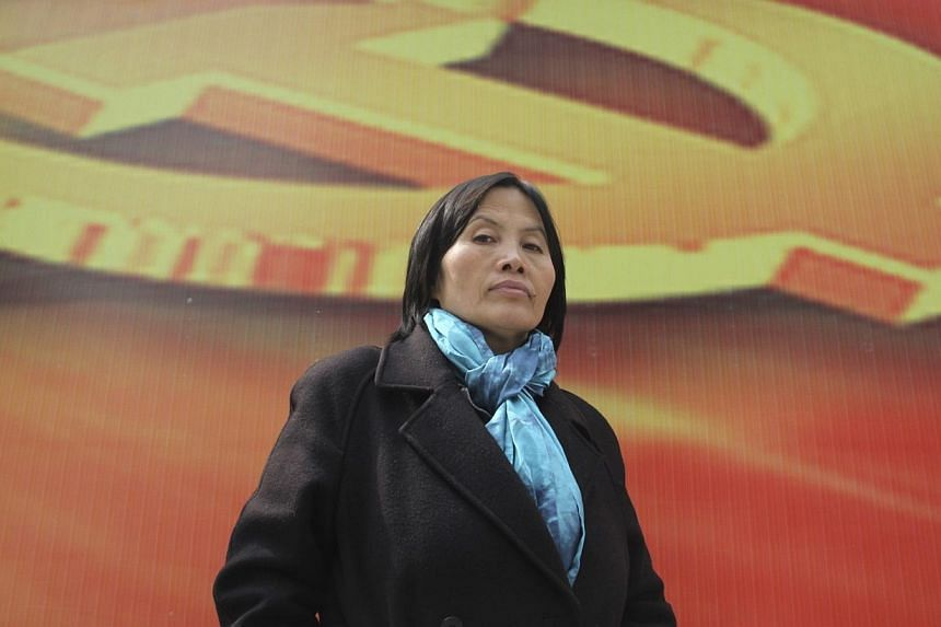 """Prominent Chinese human rights activist Cao Shunli stands in front of an emblem of the Chinese Communist Party during an interview in the central business district of Beijing on March 23, 2013.The United States is """"deeply disturbed"""" by reports"""