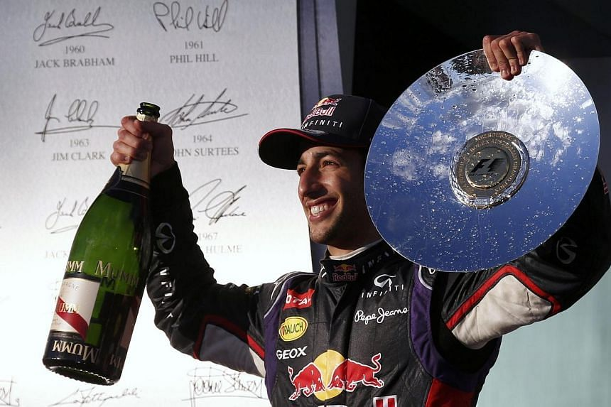 Second-placed Red Bull Formula One driver Daniel Ricciardo of Australia celebrates with his trophy and a bottle of champagne after the Australian F1 Grand Prix at the Albert Park circuit in Melbourne on Sunday, March 16, 2014. Daniel Ricciardo's