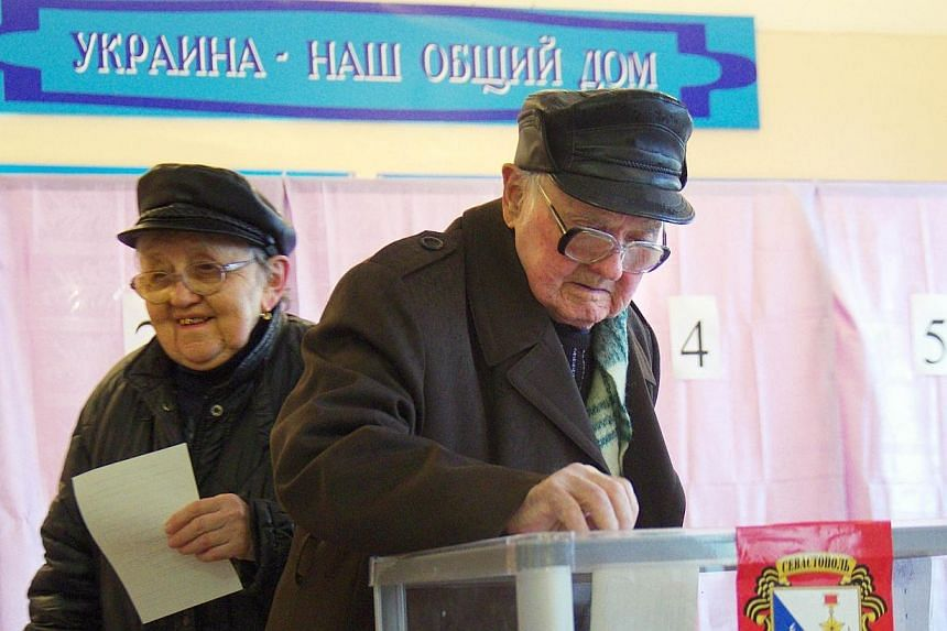 """Elderly people cast their ballots in front of a placard reading """"Ukraine is our common home"""" in one of the polling stations in Sevastopol on Sunday, March 16, 2014.China abstained from voting on a United Nations Security Council resolution to c"""
