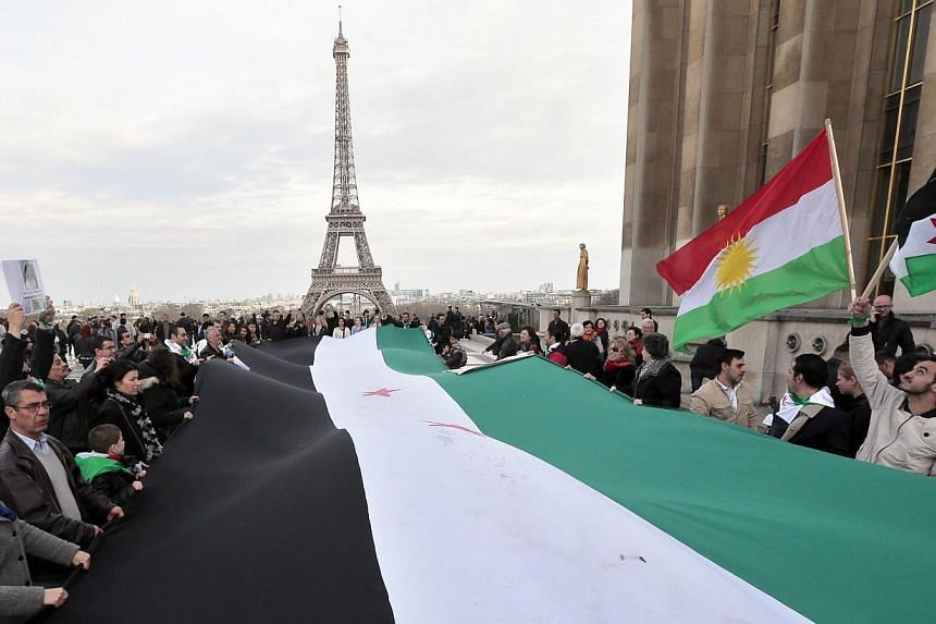 People hold a Syrian national flag as they gather in front of the Eiffel tower on March 15, 2014 in Paris, during a demonstration to mark the third anniversary of the Syria's civil war. -- PHOTO: AFP
