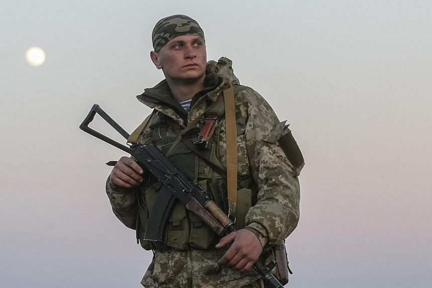"A Ukrainian serviceman guards a check point near the village of Salkovo in Kherson region, March 15, 2014. Ukraine accused Russia on Saturday of invading a region bordering Crimea and vowed to use ""all necessary measures"" to ward off an attack that c"
