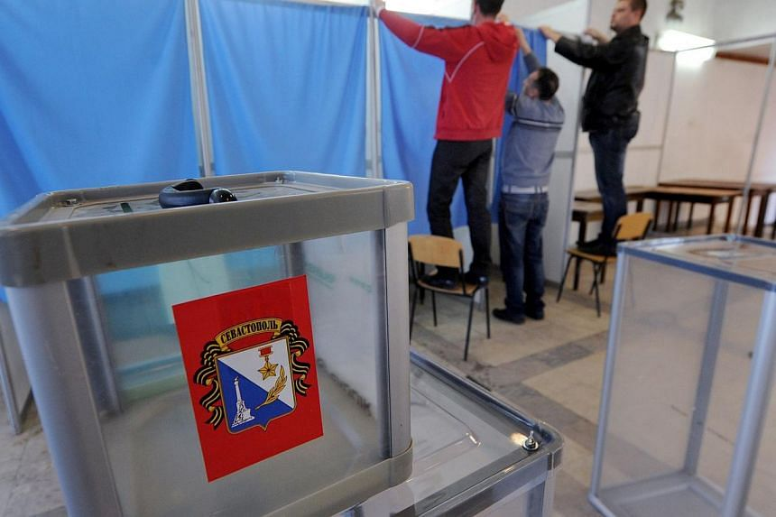 Employees prepare the polling booth in one of the polling stations of Sevastopol on March 15, 2014, on the eve of the referendum in Crimea. -- PHOTO: AFP