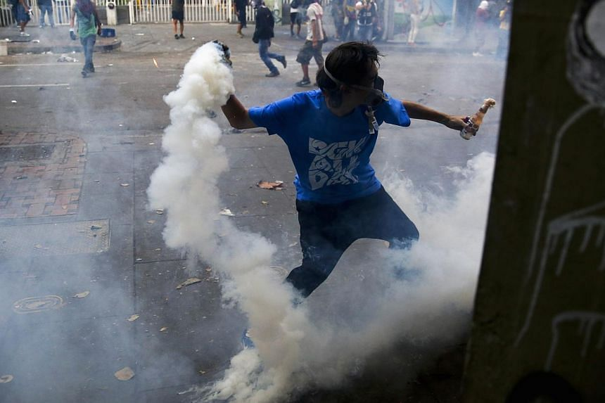 An anti-government protester throws a tear gas canister back at police during clashes in Caracas on March 15, 2014. -- PHOTO: REUTERS