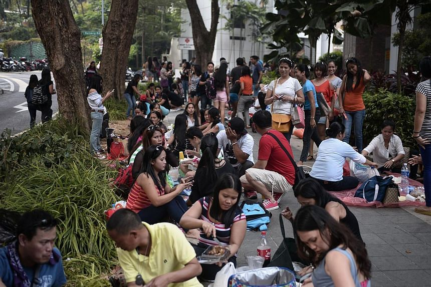 A crowd mostly having picnics in their own groups opposite Lucky Plaza at Tong Building on a recent Sunday. As more maids get days off, traditional hang-outs like Lucky Plaza and City Plaza are getting more crowded on Sundays. But some businesses say