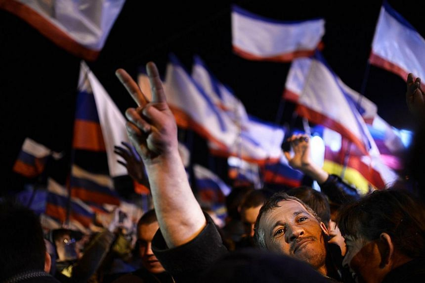 A Crimean man makes the victory sign as he celebrates in Simferopol's Lenin Square on March 16, 2014, after exit polls showed that about 95 per cent of voters in Ukraine's Crimea region supported union with Russia. -- PHOTO: AFP