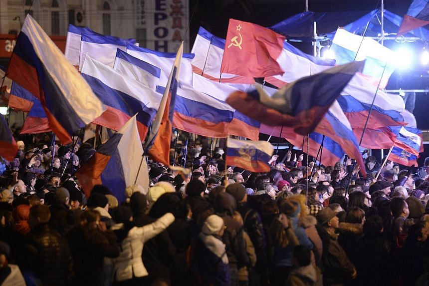 Pro-Russian Crimeans wave Russian flags as they gather to celebrate in Simferopol's Lenin Square on March 16, 2014, after exit polls showed that over 95 per cent of voters in Ukraine's Crimea region supported union with Russia. -- PHOTO: AFP