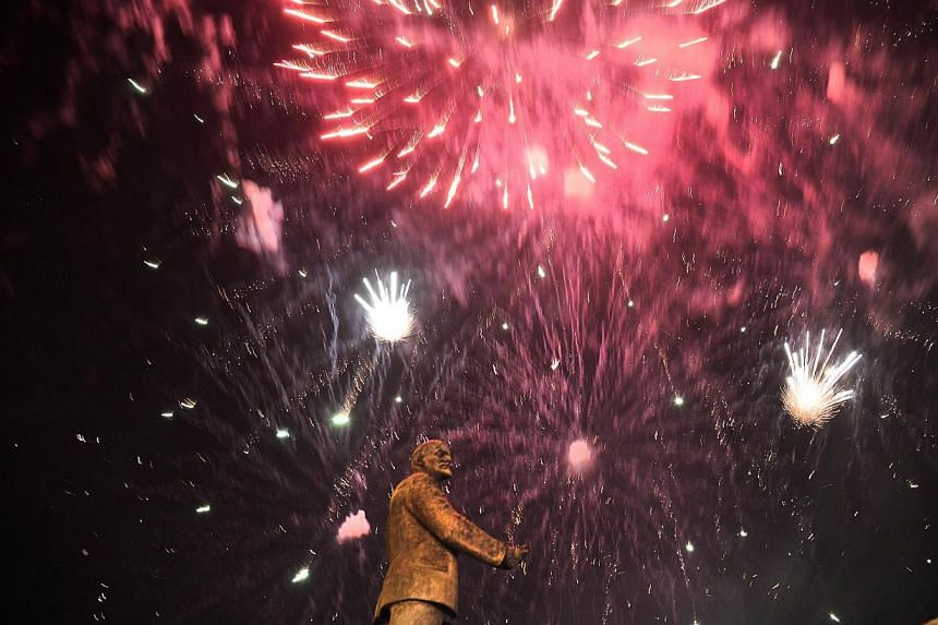 Fireworks explode behind the monument of the Soviet Union founder Vladimir Lenin in Simferopol on March 16, 2014, after partial votes showed that about 95.5 per cent of voters in Ukraine's Crimea region supported union with Russia. -- PHOTO: REUTERS