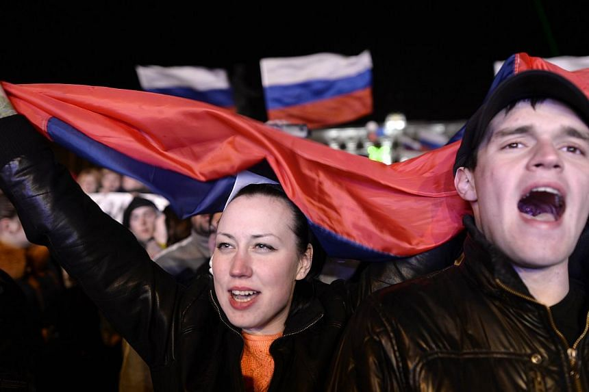 People sing the Russian national anthem as they celebrate in Simferopol's Lenin Square on March 16, 2014, after exit polls showed that about 95.5 per cent of voters in Ukraine's Crimea region supported union with Russia. -- PHOTO: AFP
