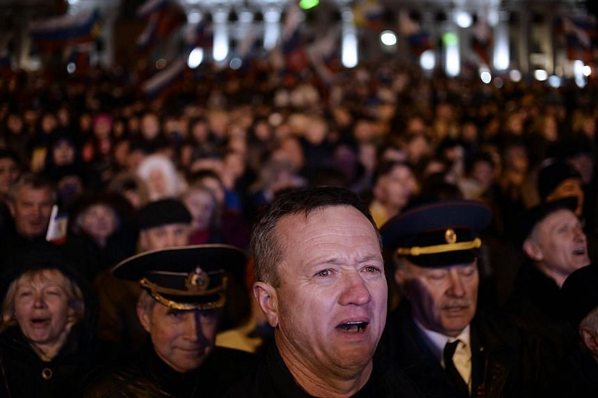 Pro-Russian Crimeans gather to celebrate in Simferopol's Lenin Square on March 16, 2014, after exit polls showed that over 95 per cent of voters in Ukraine's Crimea region supported union with Russia. -- PHOTO: AFP